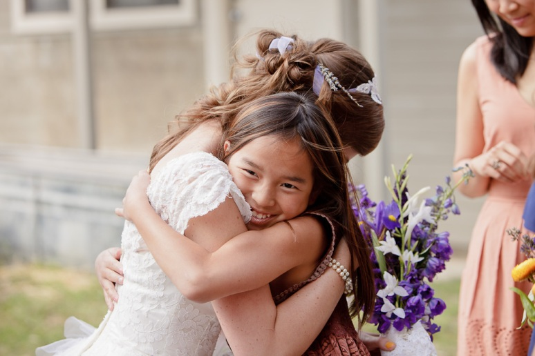 Bride Hugging Flower girl at their outdoor barn wedding at a ranch in Sonoma