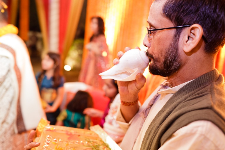 New Delhi Indian Wedding Photographer Hindu Priest Blowing Conch