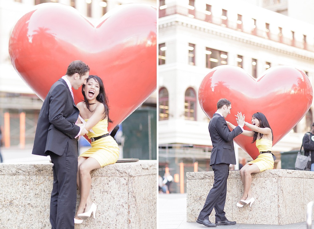 Couple laughing in front of heart during San Francisco Engagement Session in Union Square