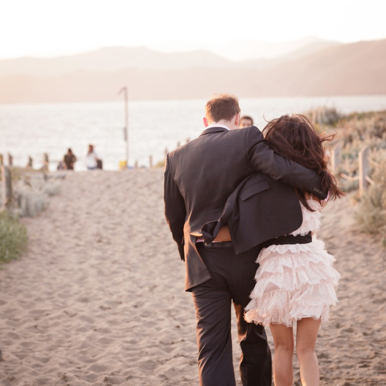 Bride and groom walking down to Baker Beach in San Francisco during their engagement session