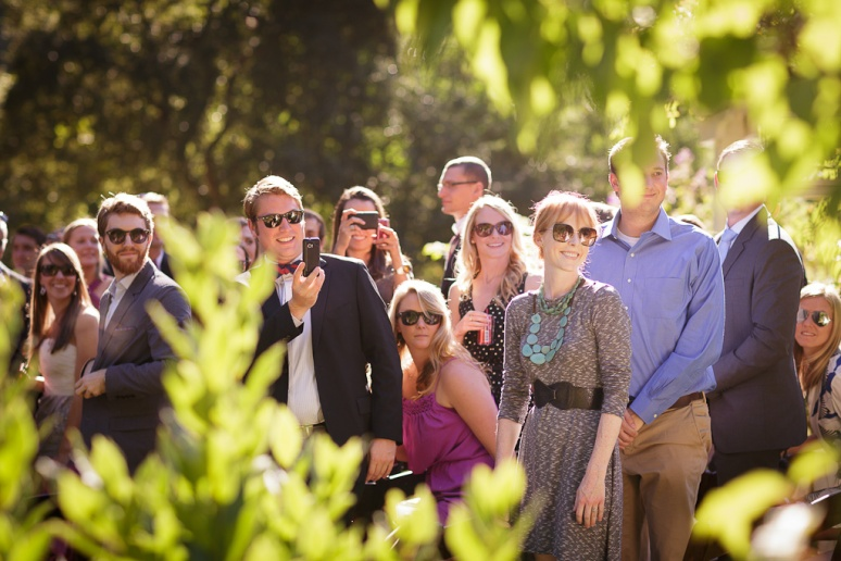 Wedding Photojournalism shot of guests watching bride walk down the aisle
