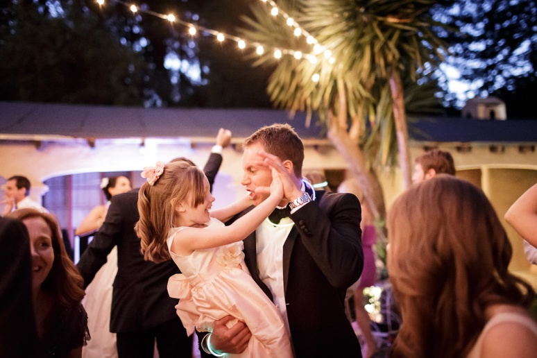 groom dancing with the flowergirl under string lights at the castle house and gardens in santa cruz
